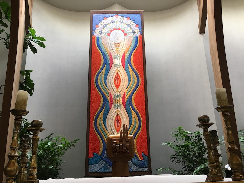 altar with tapestry in background of bread and wine water baptism