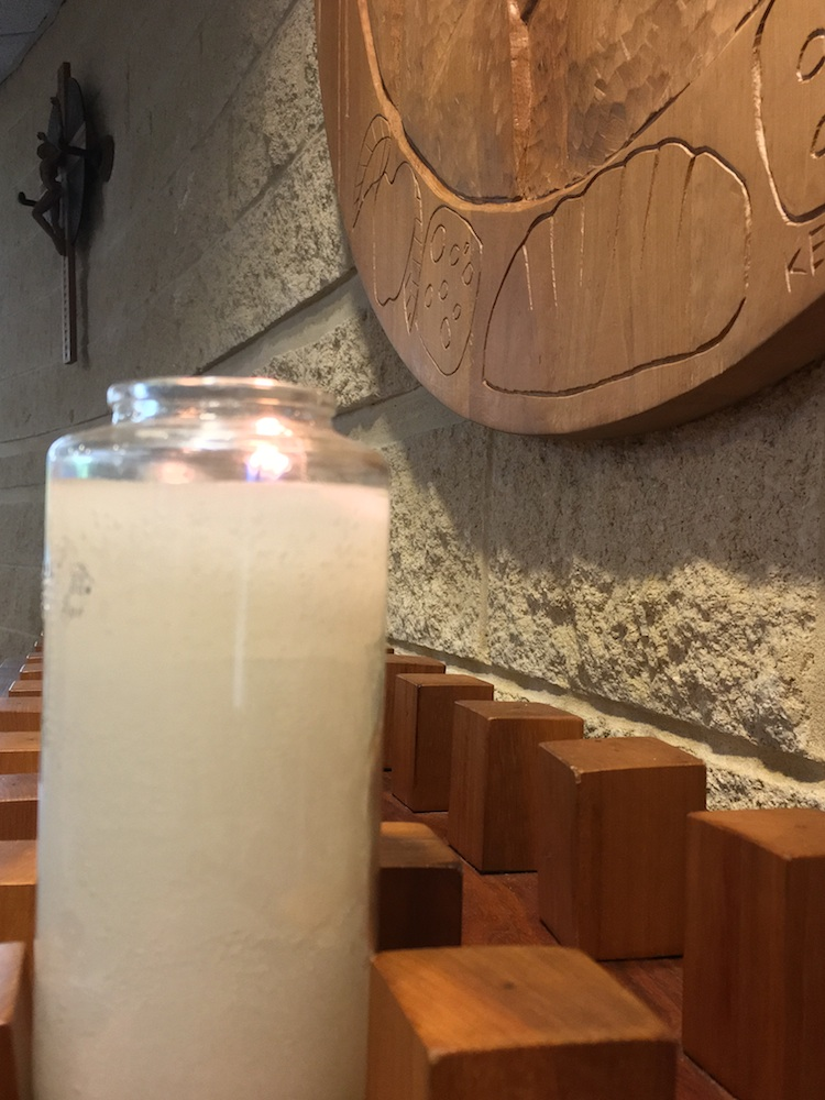 Lighted candle with cruxific of Jesus Christ and bread in background