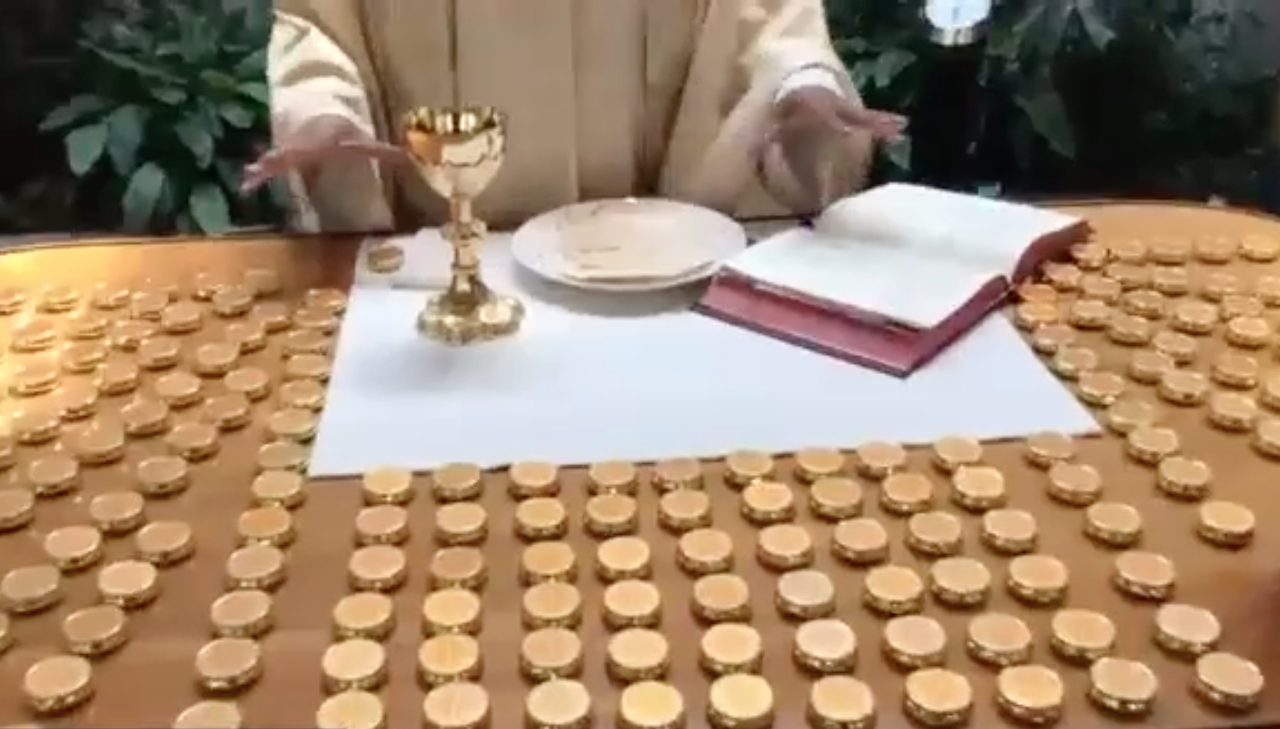 Priest hands over altar with bread, wine, and many Eucharist pyx