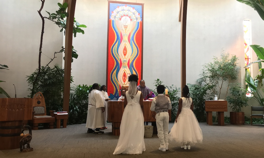 children dressed in white approaching Catholic Mass altar in preparation of first communion