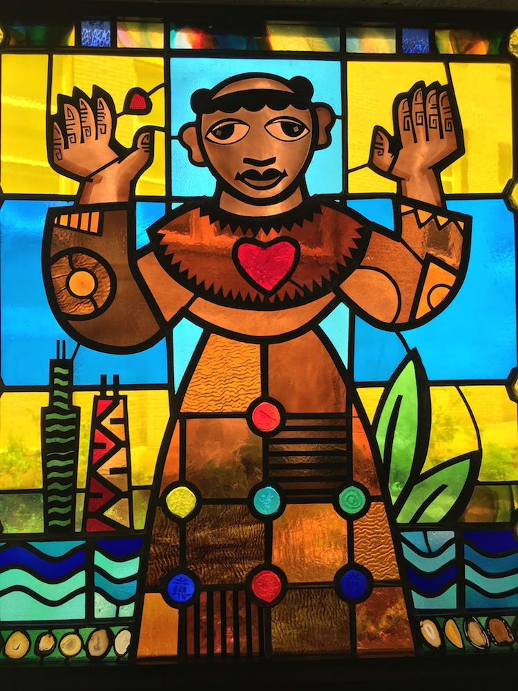 Colored stained glassed church window of saint Benedict the African with heart
