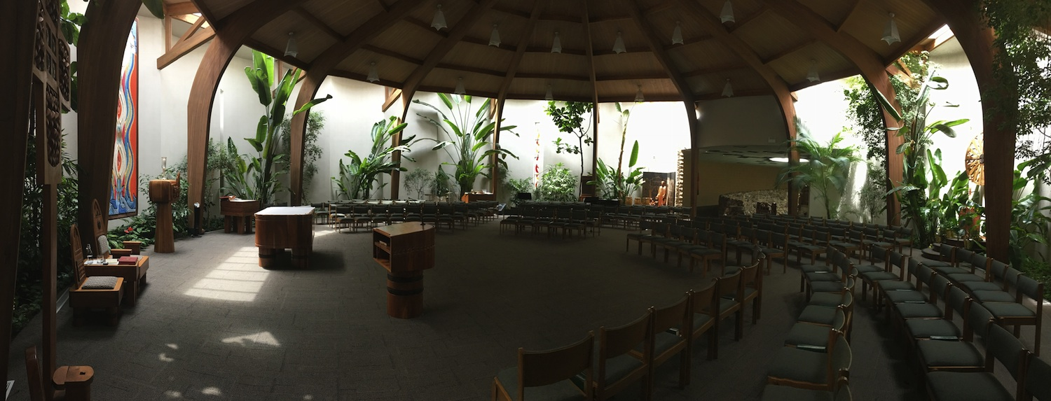 Saint Benedict the African wooden sanctuary hut for Catholic Mass celebration with green plants surrounding seats.