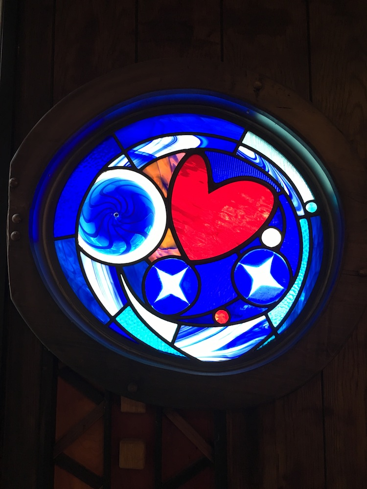 Circular window in the front church door with heart.